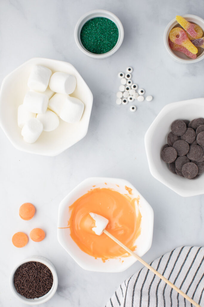 Dipping marshmellows in melted chocolate for Monster Candy Kabobs